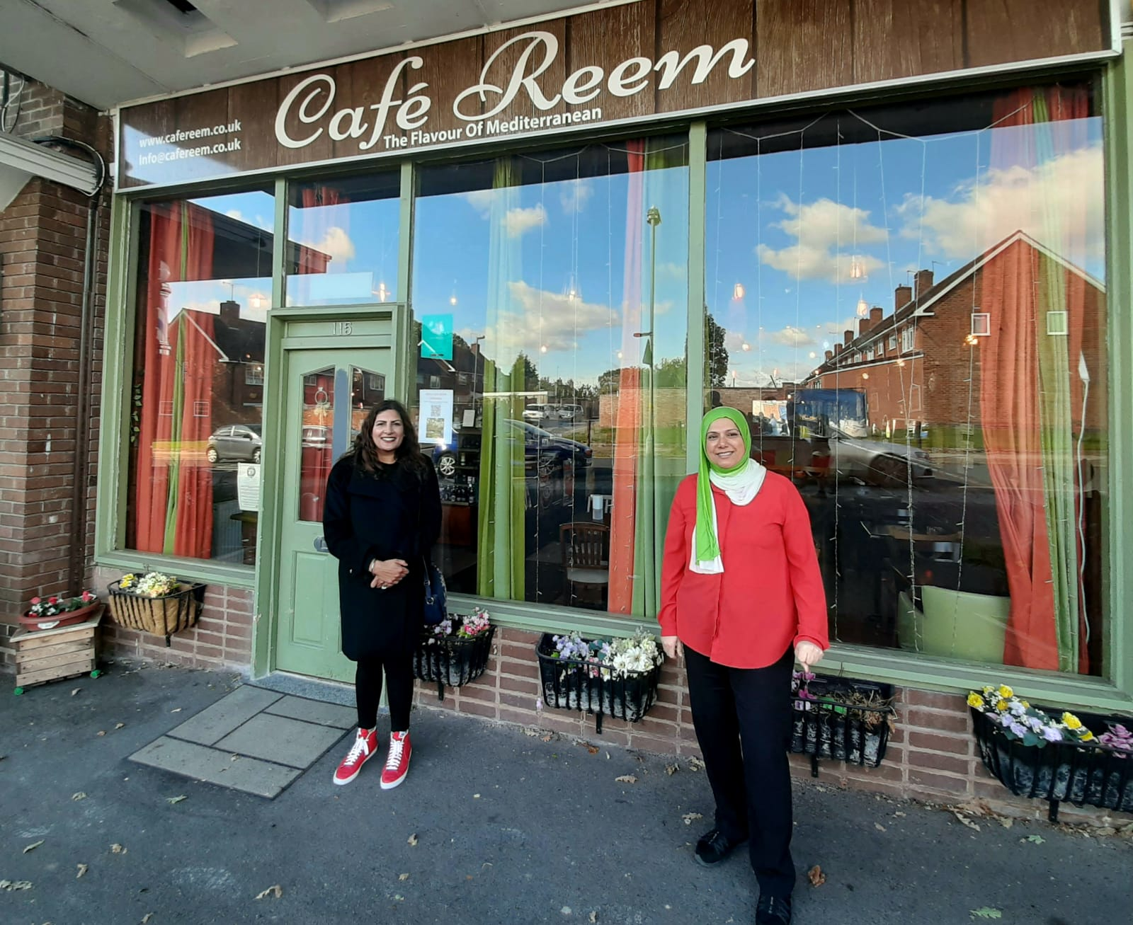 Preet meeting a business owner outside their cafe called Reem.