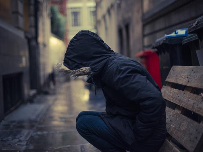 Man in hooded coat knelt down in alley