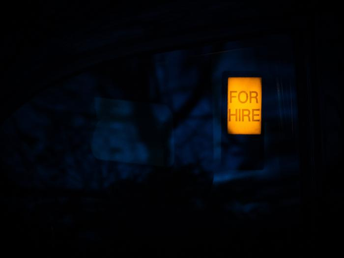 A For Hire sign lit up set against a dark background captured by The BlowUp